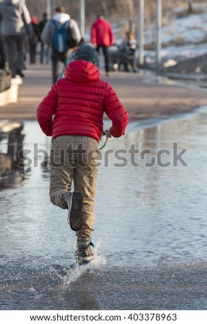 A boy in a red jacket on a scooter in a park in early spring. Sunny spring day. Splash in a puddle on a scooter - stock photo