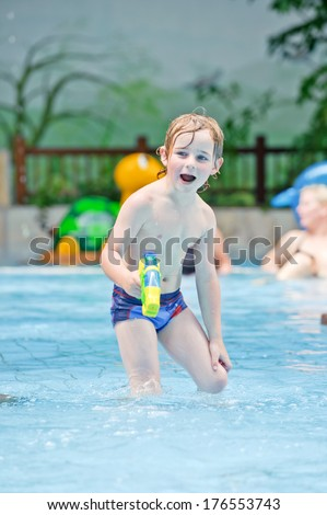 A boy in a swimming pool playing with a water gun. - stock photo