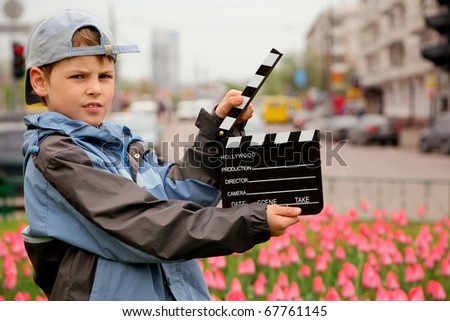 A boy in jacket and cap with cinema clapper board in hands standing on field with tulips on of urban streets - stock photo