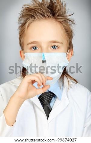 A boy in medical uniform holding a syringe. Education. - stock photo
