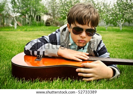 A boy in sunglasses playing the guitar on the grass - stock photo