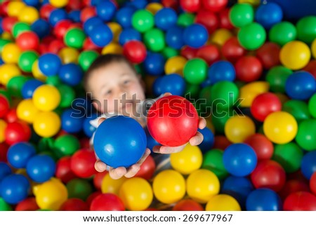 A boy in the playing room with many little colored balls. - stock photo