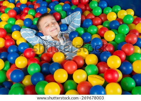A boy in the playing room with many little colored balls. Close portrait - stock photo