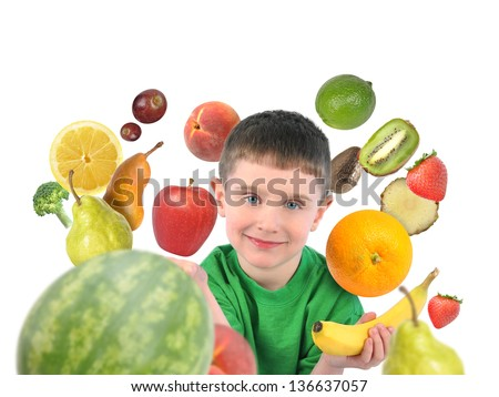 A boy is holding a banana and apple with a variety of fruit food around the child. There is a white isolated background for a diet concept. - stock photo