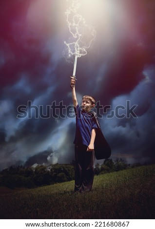 A boy is holding a sword and wearing a super hero cape with lightning bolts coming out of the sky for a imagination or pretend play concept. - stock photo
