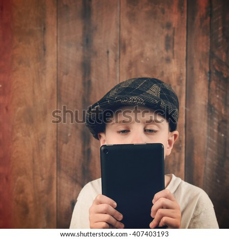 A boy is holding a technology tablet and reading a screen. The child is wearing a vintage cap with a wood background for a communication or electronic idea. - stock photo