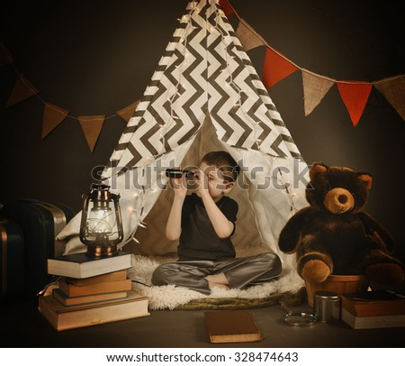 A boy is sitting in a tepee tent at night with  a light, books and teddy bear. He is looking up with a monocular for a exploration or camping concept. - stock photo