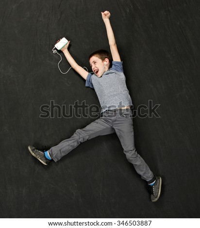 A boy jumping into the air as he listens to music - stock photo