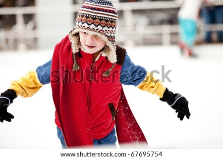 A boy just learning to ice skate. - stock photo