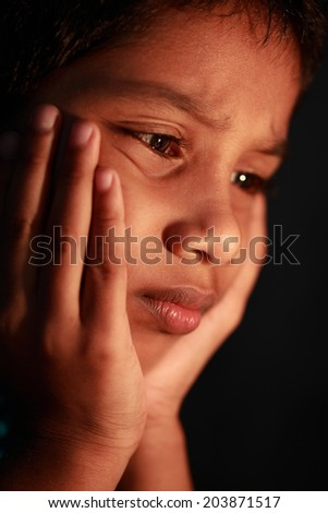 A boy looks  in a depressed mood. Focus on eyes with shallow depth of filed - stock photo