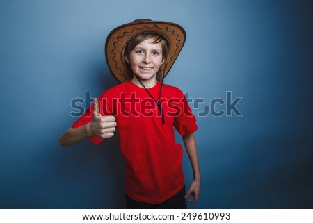 a boy of twelve European appearance cowboy hat, a gesture so on a gray background - stock photo