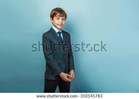 a boy of twelve European appearance in a suit is smiling portrait on a gray background - stock photo