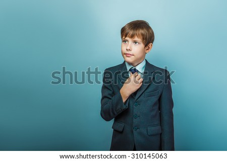 a boy of twelve European appearance in a suit straightens his tie on a gray background - stock photo