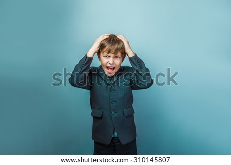 a boy of twelve European appearance in a suit yells opened his mouth keeps his hands on his head on a gray background - stock photo