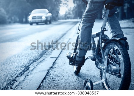 A boy on bike and a car on the road - stock photo