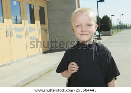 A boy on the playground of his school with a backpak - stock photo