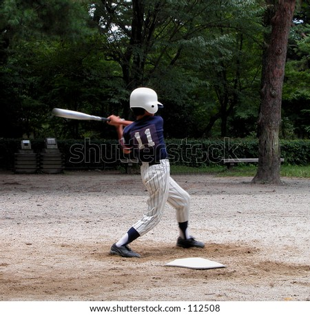 A boy playing baseball in a park - stock photo