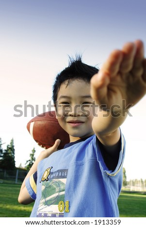 A boy playing football outdoor - stock photo