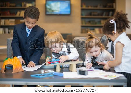 A boy playing with a toy train, others play with stationery in the business center - stock photo