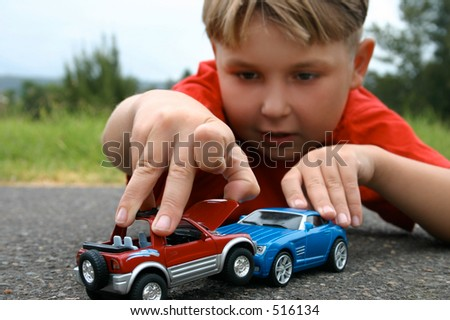 A boy playing with toy cars - stock photo