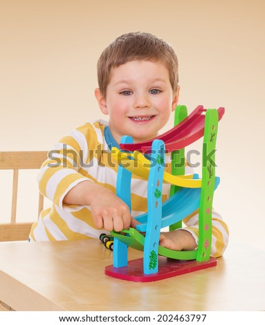 A boy plays with a toy, sitting at the table.passionate child for interesting occupation,active lifestyle,happiness concept,carefree childhood concept. - stock photo