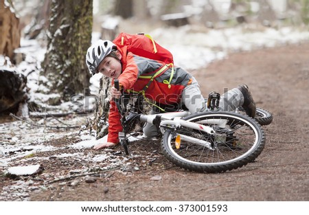 A boy riding his bike in a snow riddled forrest - stock photo
