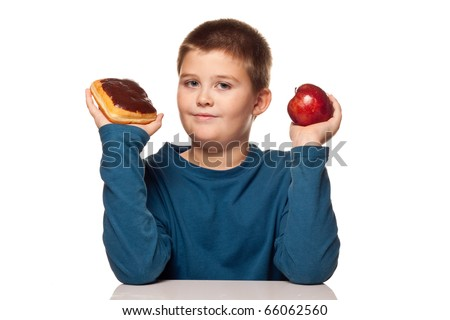 a boy's choice of a healthy or unhealthy snack - donut or apple - stock photo