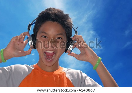 A boy singing while listening to music on his headphone - stock photo