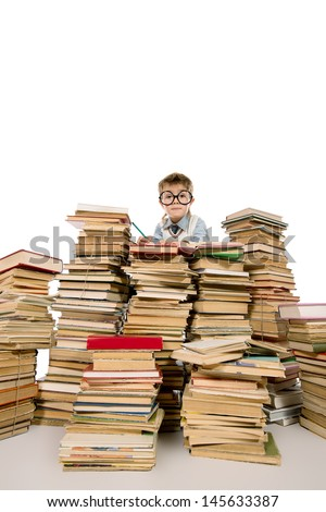 A boy sitting on a pile of books and reading a book. Education. Isolated over white. - stock photo