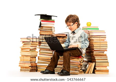 A boy sitting on a pile of books with a laptop on his knees. Education. Isolated over white. - stock photo
