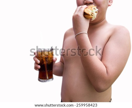 A boy standing and eating a hamburger with a sweet cold beverage from a soda cup in his hand - stock photo