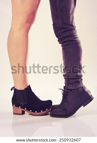A boy standing on his toes to reach her tall girlfriend and kiss her - stock photo