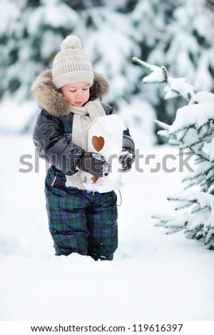 A boy stands in the snow. A child in a winter forest. - stock photo