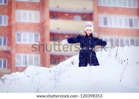 A boy stands on a snowy mountain. Hand in hand. Winter and cold. A child playing outdoors. In the background the high house. Happy baby. - stock photo