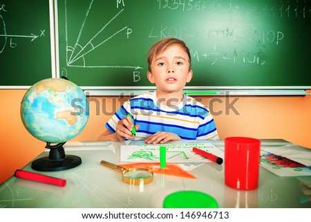 A boy studying in classroom at school. Education. - stock photo