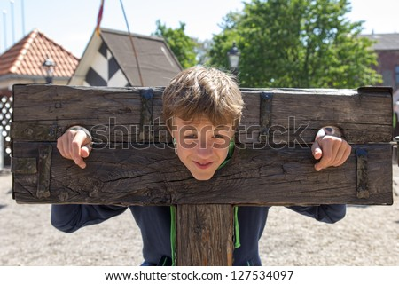 a boy trapped in a medieval torture device - stock photo