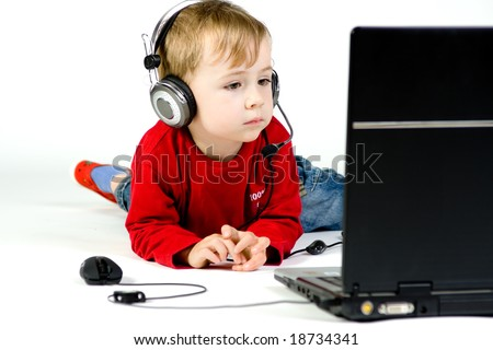 A boy watching a movie or listening to music on a laptop. - stock photo