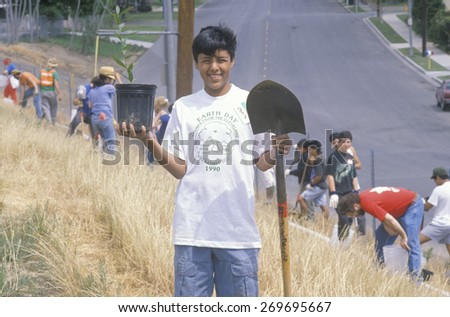 A boy wearing an Earth Day t-shirt participating in a tree planting by the Clean & Green volunteers of the Los Angeles Conservation Corps - stock photo