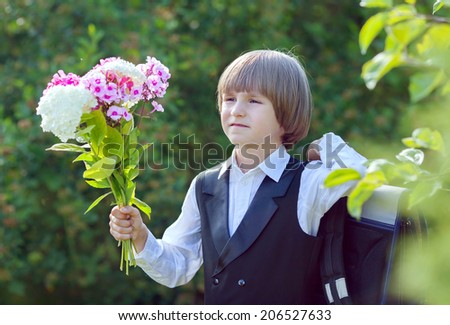 a boy with a bouquet goes to school on the first of September - stock photo