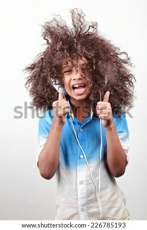 A boy with a funky hairstyle in a playful mood - stock photo
