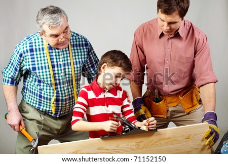 A boy working with plane under his father and grandpa?s supervision - stock photo