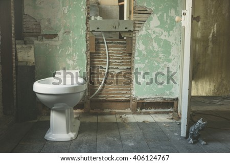 A brand new toilet fitted in an old derelict room being converted to a bathroom - stock photo