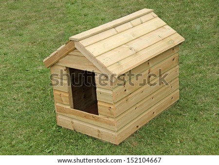 A Brand New Wooden Dog Kennel on a Grass Lawn. - stock photo