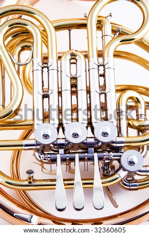 A brass and copper French horn isolated against a white background close up in the vertical format. - stock photo