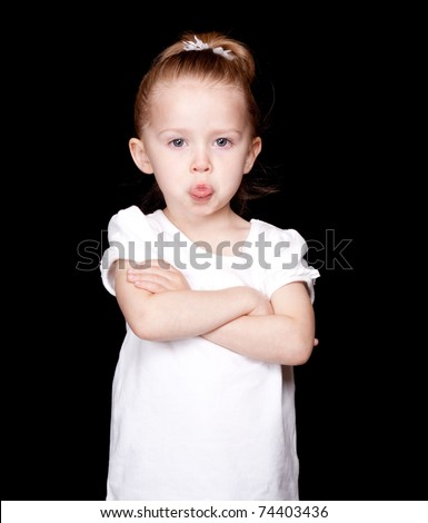 A bratty but cute little girl sticking her tongue out at the camera. - stock photo