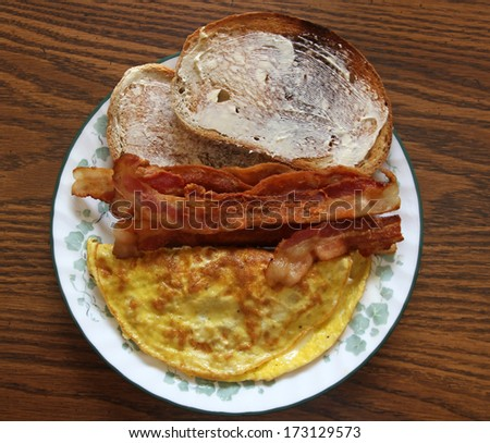 A breakfast meal of an egg omelet, bacon, and toast  - stock photo