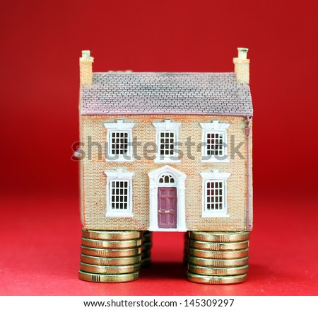 A brick house place on good financial foundations, with a great red background asking the question are you ready to purchase this red hot property. - stock photo