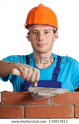 A bricklayer in an orange helmet. - stock photo
