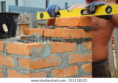 A bricklayer using a level to check his new wall outdoor - stock photo