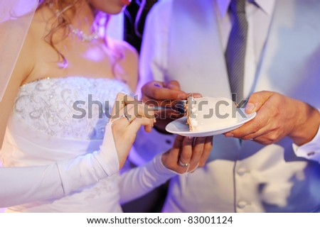 A bride and a groom are eating their wedding cake - stock photo